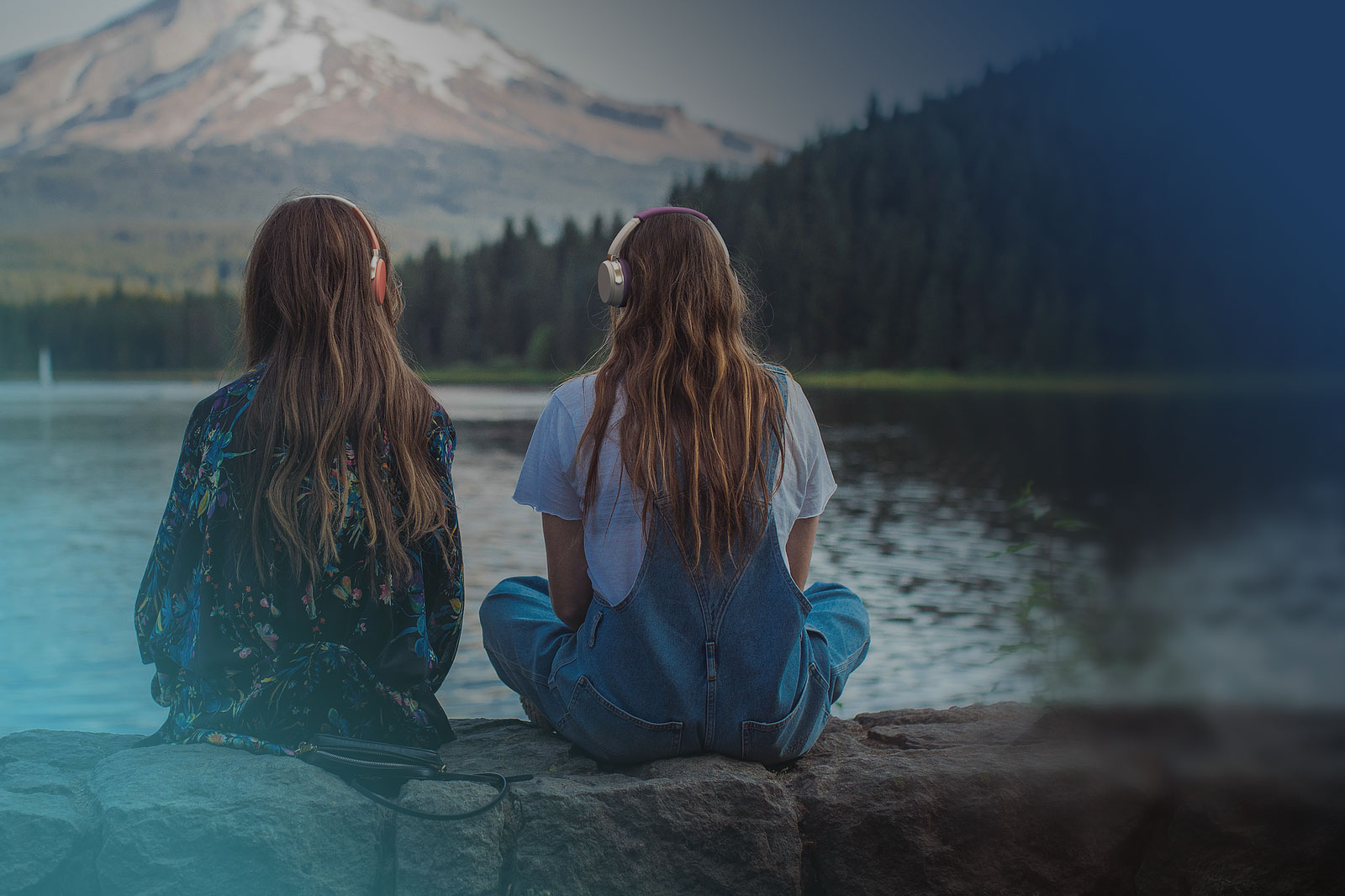 Two women sitting by a lake, wearing sustainably sourced headphones by VOYAGR