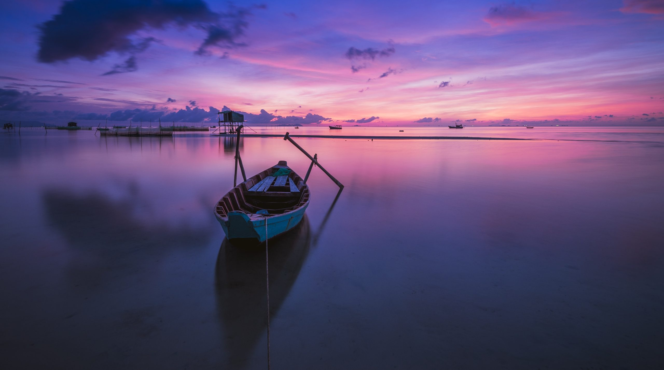 A boat docked in front of a sunset