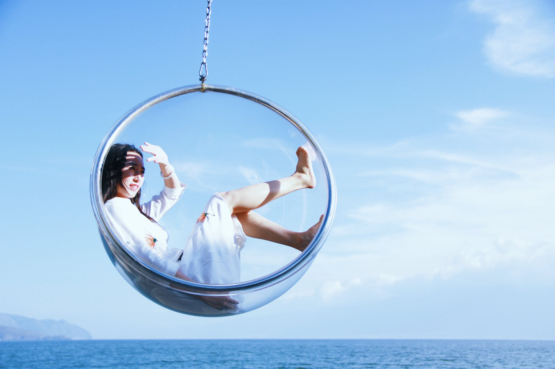 A young woman in a swinging seat hanging over the sea